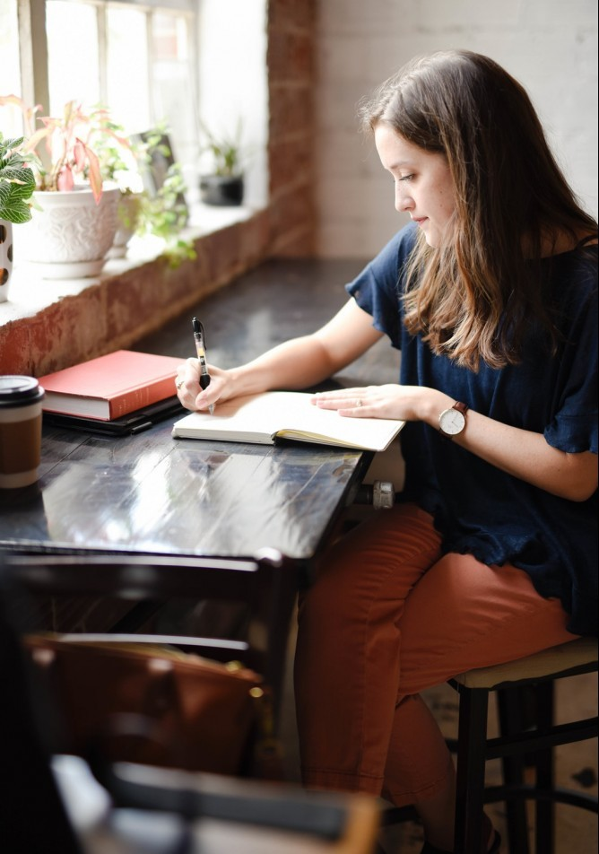woman working diligently at writing