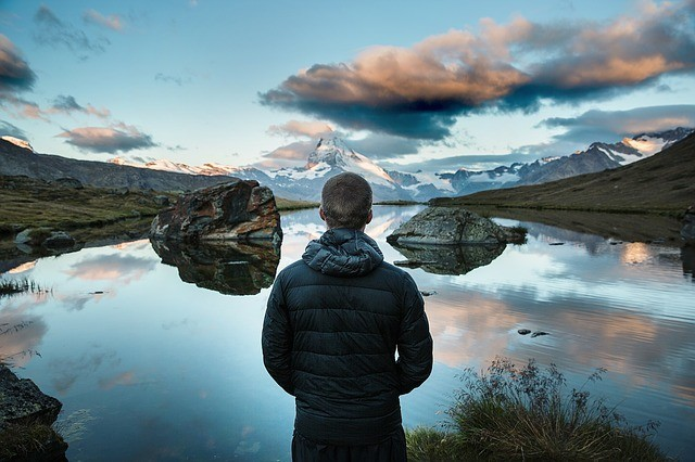 calm man looking at pond with mountain in background