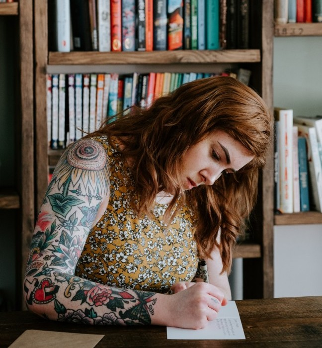 caucasian woman with tattoos writing in journal
