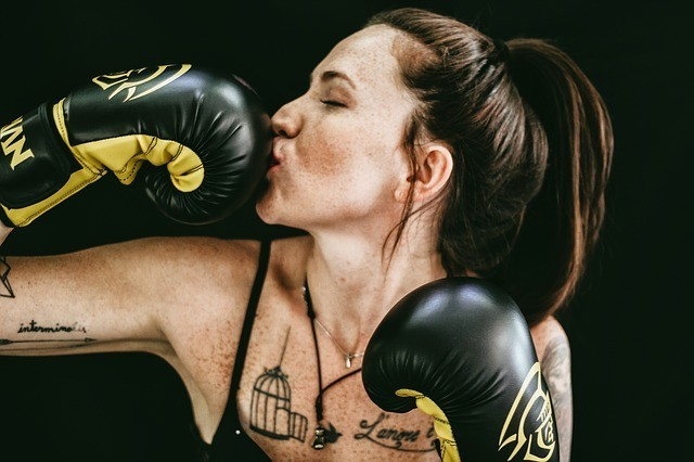 woman in wearing boxing gloves and exercising