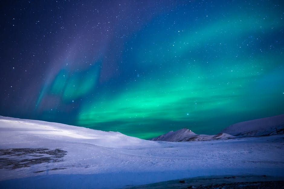 aurora borealis with green light over snowy land