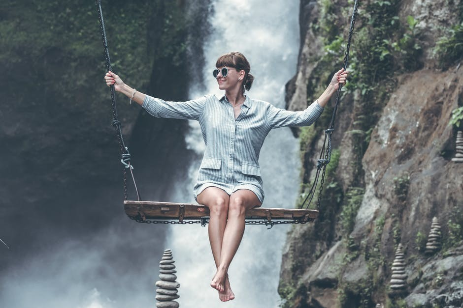 smiling woman on swing over waterfall and cliffs