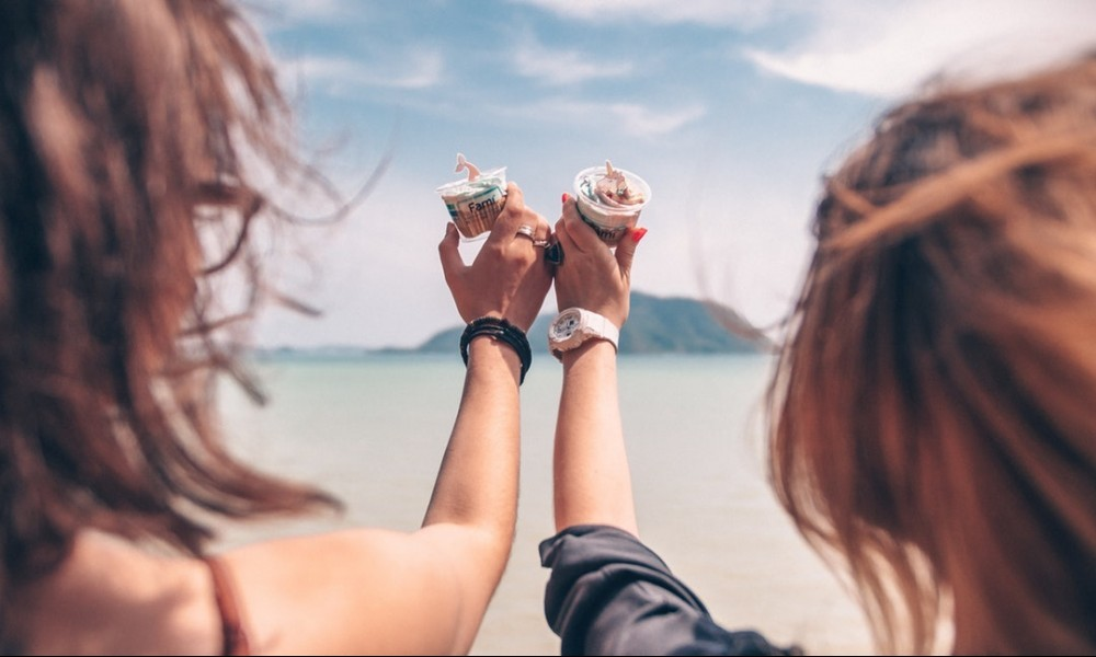 two women holding up a treat and looking at the beach